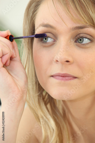 a woman putting mascara