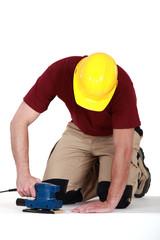 Builder using sander on floor