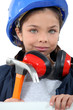 Child with a hammer, hardhat and ear defenders