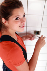 Tradeswoman fixing an electrical outlet