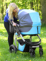 Young mother with baby stroller  walking in the park.
