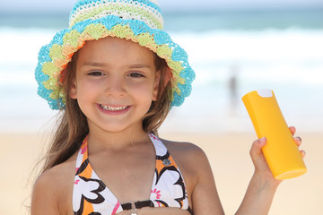 little girl on the beach with a sun cream