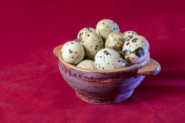 Quail eggs in clay bowl, red background