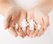 womans hands with paper man family