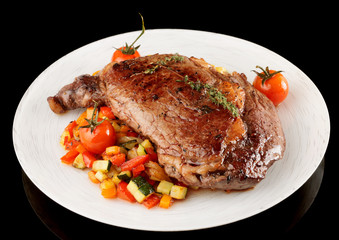 Tasty ribeye steak with stir fried vegetables isolated on black