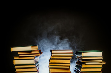 Smoldering stack of old books with smoke rising
