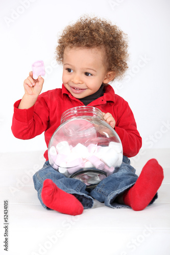 Little boy eating marshmallows from jar