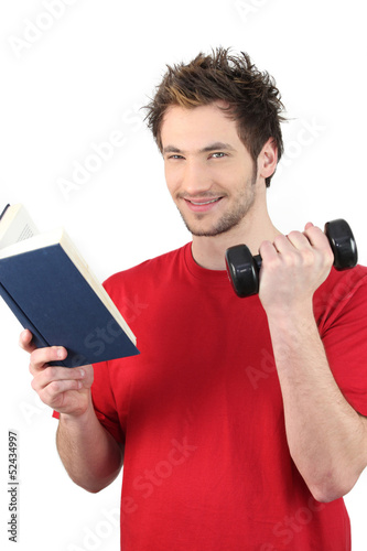 Man reading book whilst lifting weights