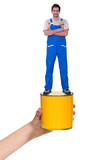 Decorator standing on a pot of paint