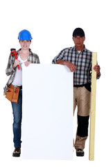 Plumber and carpenter stood by blank poster