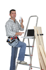 Carpenter standing by a ladder with  a mobile telephone