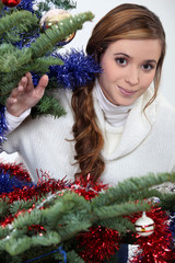 Young woman stood by Christmas tree