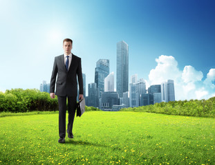 business man walking on green field and modern city