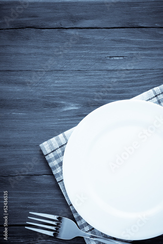 white plate and fork on wood