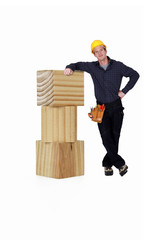 Carpenter leaning against giant blocks