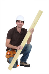 Carpenter with plank of wood