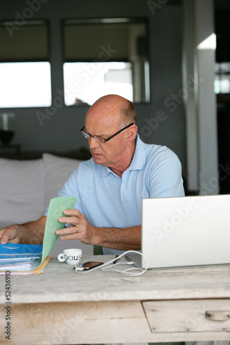 Elderly man sorting through his paperwork