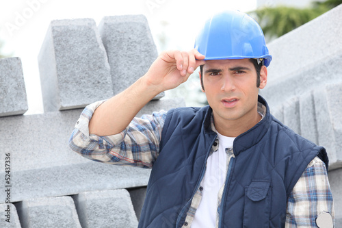 Construction worker in a hardhat next to concrete kerbing