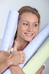 Woman holding rolls of wallpaper