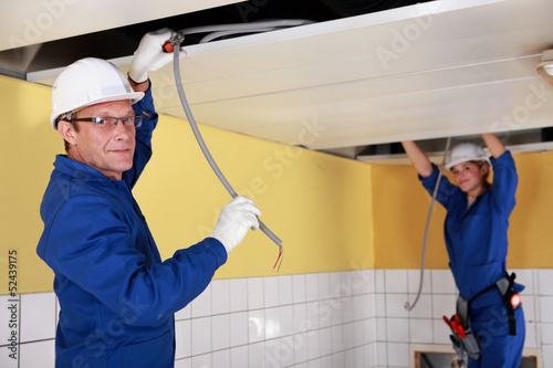Two electricians working on false ceiling