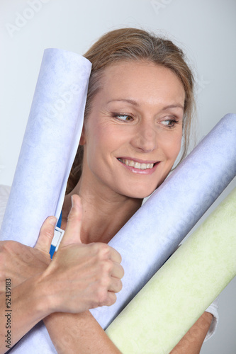 Woman holding rolls of wallpaper