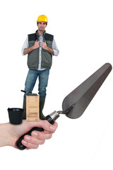 Bricklayer standing on a hand holding a trowel