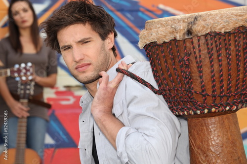 Young man carrying a djembe