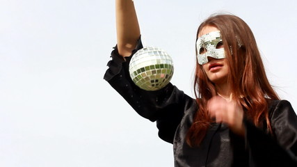 The girl in a black cloak. In the hands holding a mirror ball.