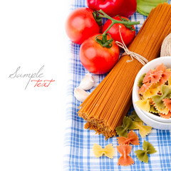 Italian pasta and vegetables on tablecloth over white background