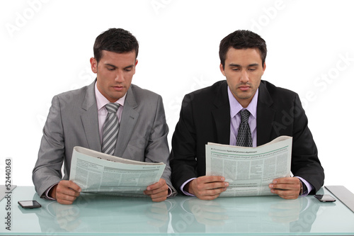 Two businessman sat with newspapers