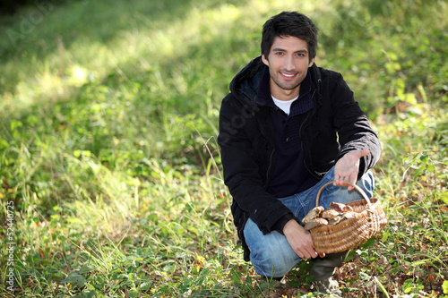 Man knelt by basket of mushrooms