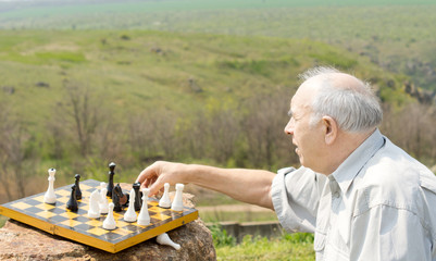 Retired man playing chess in the countryside