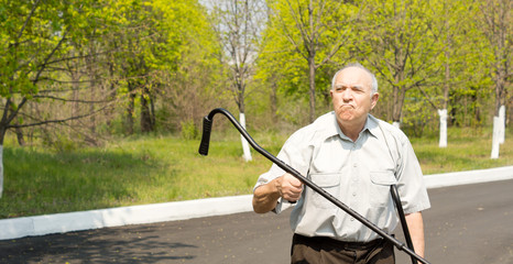 Elderly man waving his crutch in the air