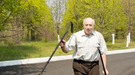 Senior man walking on crutches