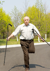 Elderly disabled man balancing on one leg