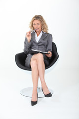 businesswoman sitting cross-legged with a flirtatious look
