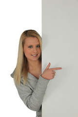 Blond girl pointing at blank panel