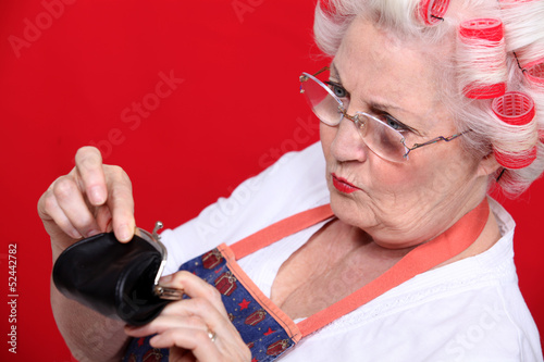 Old woman looking money in her purse