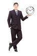 Full length portrait of a young man in suit holding a clock