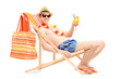 Smiling young male on a beach chair drinking cocktail