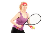 Middle aged female holding tennis racket and ball