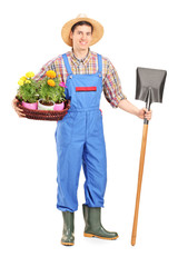 Male agricultural worker holding a shovel and flowers