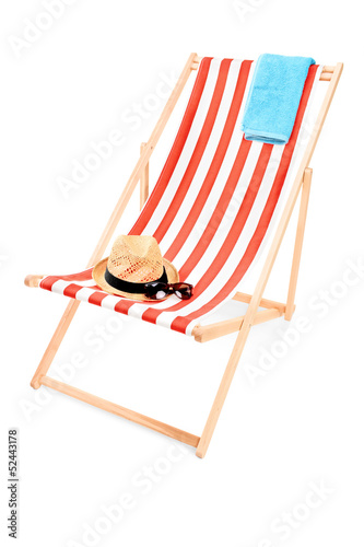 Studio shot of a sun lounger with towel, hat and sunglasses