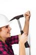 Junge Heimwerkerin klopft Nagel in die Wand