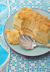 Napoleon cake on a plate on blue tablecloth
