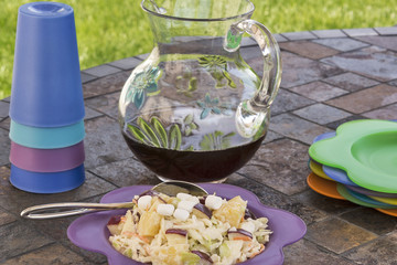 Coleslaw with a pitcher of iced tea at a picnic