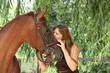 Girl in dress and brown horse portrait in forest