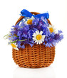 Beautiful bouquet of cornflowers and chamomiles in basket,