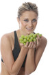 Model Released. Young Woman Holding a Bunch of Grapes