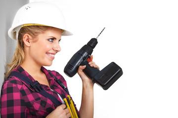 Junge Heimwerkerin mit Akkubohrer lacht